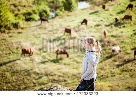 Beautiful sportive blonde girl standing on rock. Field with cows background. Copy space.