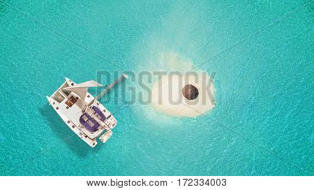 Small sandy island with umbrella and catamaran, concept of relaxation and summer vacation on beach.