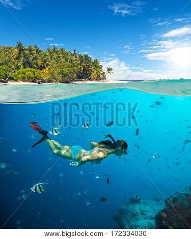 Young woman snorkeling on tropical beach. Underwater sports and tropical vacation template