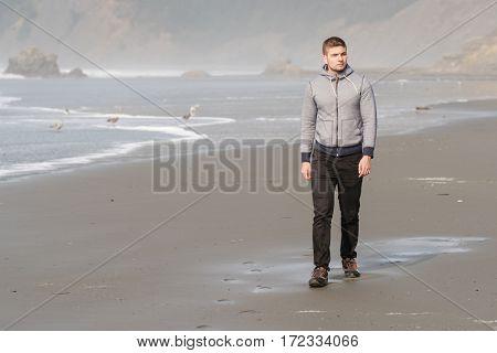 Lone man at beach, autumn. USA Pacific coast landscape, Oregon