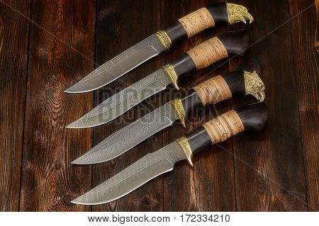 Hunting damascus steel knives handmade on a brown wooden background closeup