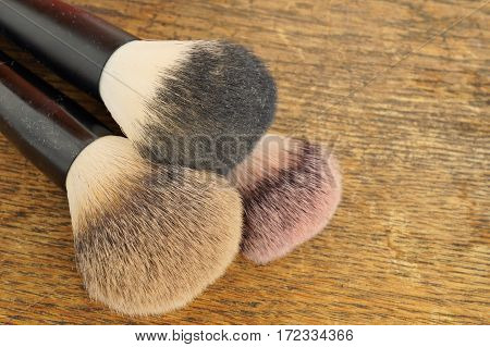 Macro detail of set of cosmetic brushes  used as applicators of make-up on wooden background as a symbol of women's cosmetics and fashion