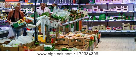 CYPRUS, PROTARAS, SUPERMARKET LIDL - 10.10.2016: People is choising products in supermarket. Fruits and vegetables on the shelves at the shop