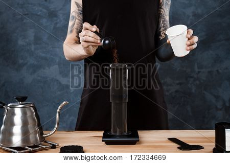 Young tattooed male barista brewing coffee. Alternative method aeropress. Copy space.