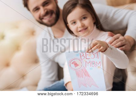 Postcard is ready. Pretty adorable nice girl holding a postcard and showing it to you while sitting together with her father