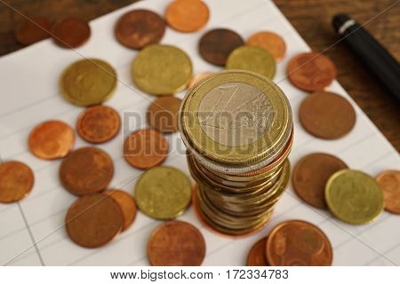Macro money background made of column of Euro coins on the lined paper notebook with many coins of various value below as a symbol of European finances