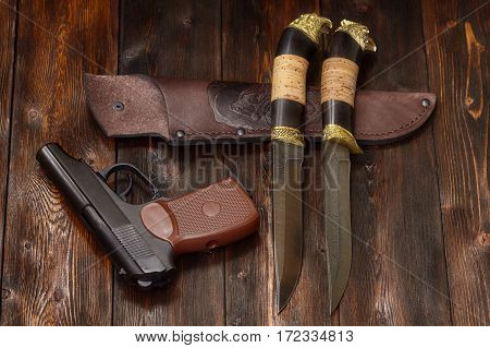 Gun and hunting damascus steel knives handmade and leather sheath on a brown wooden background closeup