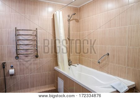 bathroom in warm colors, with a toilet, a bathtub, a hairdryer, a mirror, a dryer for clothes, a bidet and a curtain for the bath, shower and bathrobes Kobin with towels