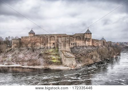 Ivangorod, Russia - January 2, 2017: View of Ivangorod Fortress museum on Russian territory from Estonian territory. Foreground is Narva (Narova) River, which is international border between two countries