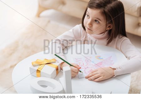 Greeting postcard. Nice pleasant cute girl holding a pencil and drawing a postcard while preparing to Mothers Day