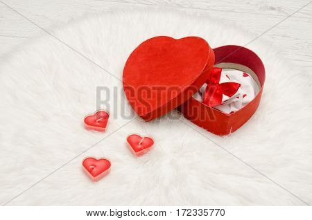 Open red box with heart shaped red and white linen on a white fur. Heart shaped candles