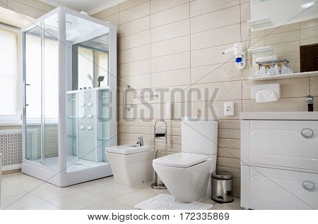 bathroom in warm colors, with a toilet, a bathtub, a hairdryer, a mirror, a dryer for clothes, a bidet and a curtain for the bath, shower and bathrobes Kobin with towels poster