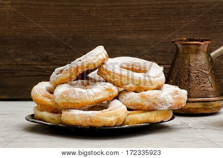 Donuts sprinkled with powdered sugar coffee pots dark wood background. Close-up side view