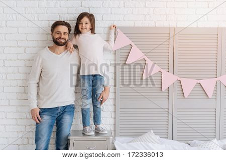 Happy parenthood. Cheerful positive bearded man standing near his daughter and hugging her while being together at home