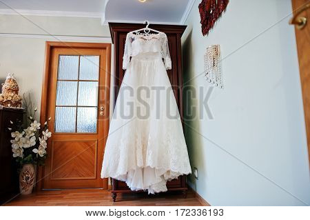 White Wedding Dress Of Bride On Hangers At Closet.