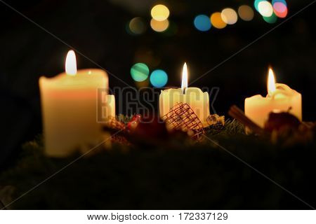 Detail of burning candles with background made of colorful bokeh lights placed on the Christmas tree as a symbol of peaceful and serene holiday time