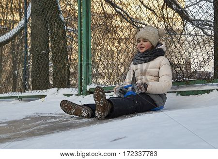 Girl sliding down on icy hill in the moscow yard