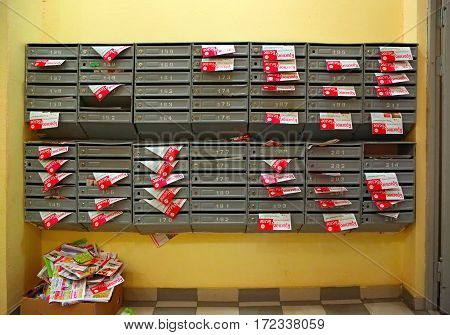 BALASHIKHA/ RUSSIA - APRIL 29, 2014: Mailboxes in the entrance hall of a residential house filled with paper flyers with the inscription in russian language Red and White. City Balashikha Russia.