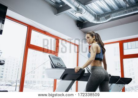 Young fit pretty woman with ponytail doing exercises on the treadmill. She has turned her head aside a little bit. Beautiful girl looks quite concentrated on a good training.