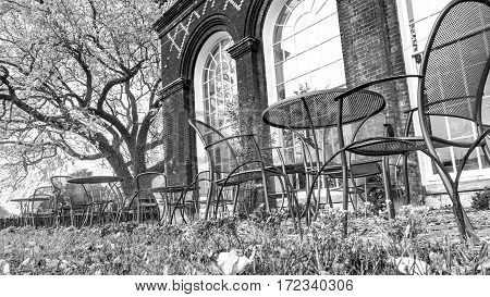 black and white: Chairs and table in an english garden with orangery in the background. It's teatime!