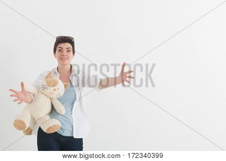 Portrait of a young girl in white shirt on the light background. Looking at the camera, smiling and extending hands forward to the spectator. Happy woman with plush toy cat.