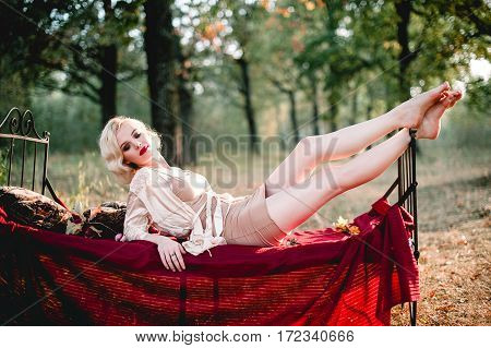 Beautiful And Elegant Blonde Woman With Red Lips And Hair Waves Wearing Beige Nightie Posing On The