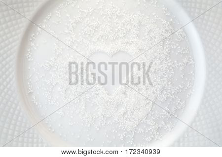 Granulated sugar in a shape of heart spilled on a white plate. Raw food ingredient background. Love for cooking concept