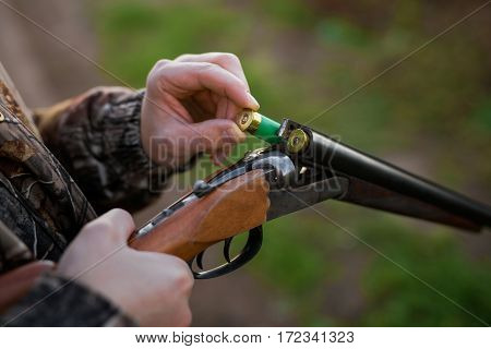 Hunter loading rifle with patron in the wild