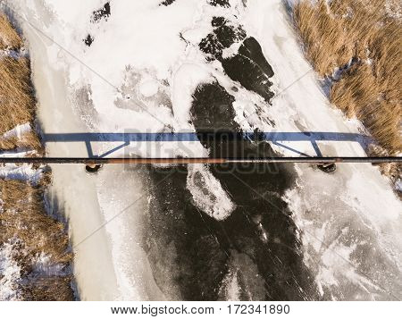 The pipe of the factory above frozen river. Steal big pipeline. Aerial view.