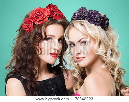 Beauty portrait. Couple of attractive blond and brunette girls with curly hair and a beautiful headband over green background.