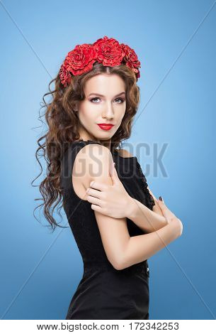 Beautiful brunette with bright red flower headband over colored blue background.
