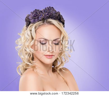 Beauty portrait of attractive blond girl with curly hair and a beautiful headband over magenta purple violet background.
