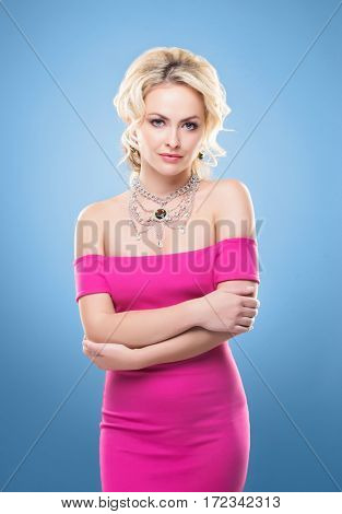 Beautiful blond girl with luxury golden necklace over blue background.