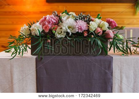 Beautifully organized event - served wedding table ready for guests, decorated with flowers. Event in restaurant outdoors. Banquet floral decor, celebration.