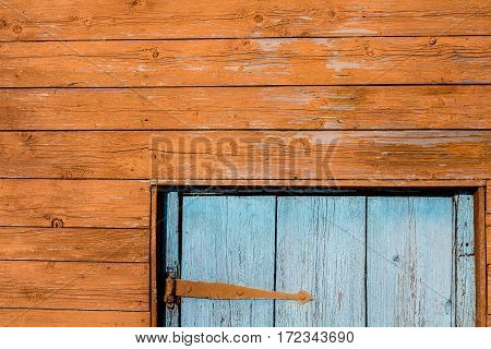 fragment of a wooden house. Orange wall and blue door.