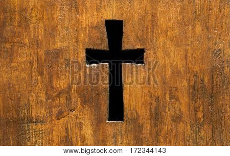 Cross shape hole in a church wooden fence