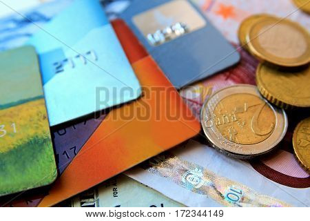 stack of multicolored credit cards and euro coins scattered around close-up.
