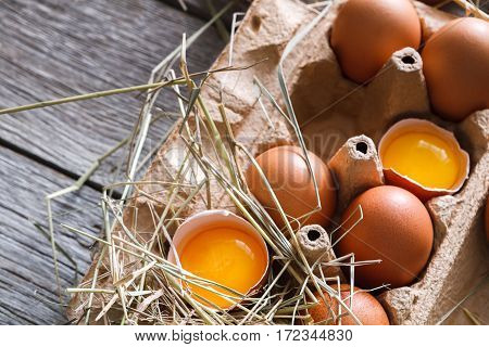 Eggs carton closeup, fresh natural healthy food background. Brown cracked eggs with bright yellow yolk on rustic wood. Organic farming concept.