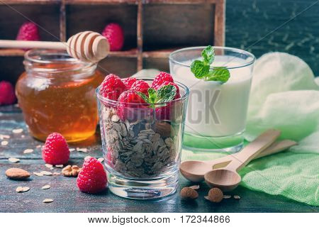 Healthy breakfast. Granola with honey, yogurt and fresh berries raspberry in a glass. Selective focus
