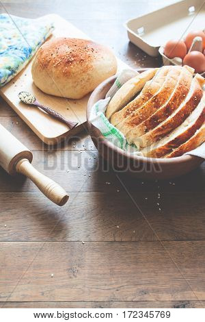 loaf of bread on wood background with eggs and bakery tools with copy space