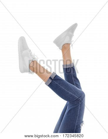 Female feet in sneakers raised up. Isolated on white background.