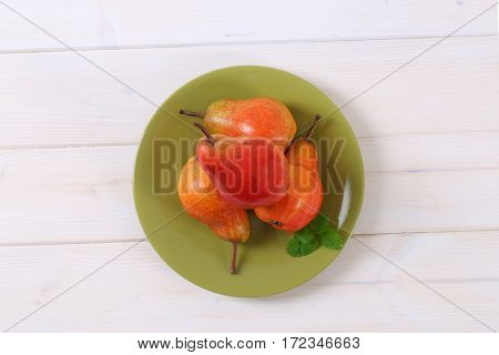 plate of ripe red pears on white background