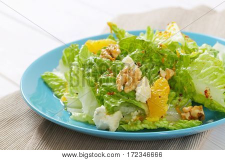 plate of chinese cabbage salad with orange, walnuts and cheese - close up