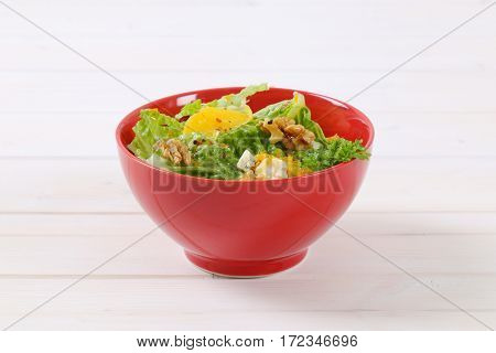 bowl of chinese cabbage salad with orange, walnuts and cheese