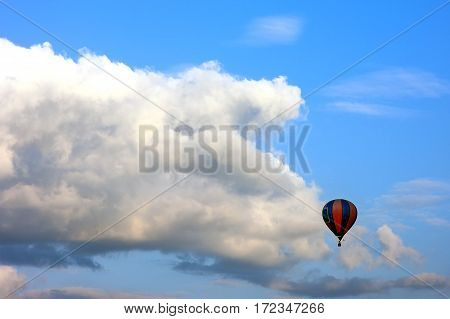 Lonely Air Baloon Flying In Front Of White Puffy Clouds Against Blue Sky