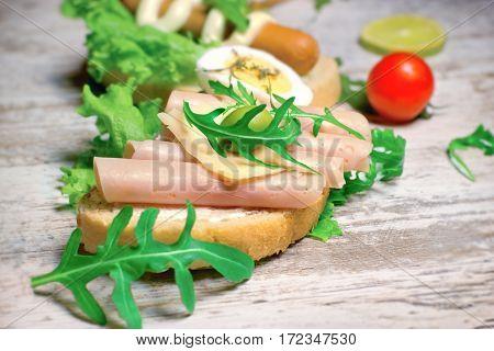 Tasty sandwich with ham and fresh green salad
