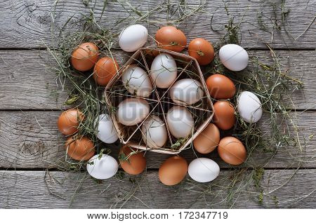 Fresh chicken eggs background. Brown and white eggs in craft carton pack on hay at rustic wood table. Top view. Rural still life, natural healthy food and organic farming concept.