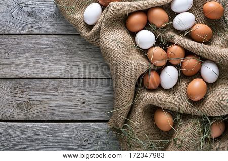 Poultry farm concept. Fresh brown and white eggs on burlap textile at rustic wood background with copy space. Top view on sacking. Rural still life, natural organic healthy food.