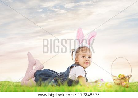Easter bunny. Little girl dressed as the Easter bunny lying on the grass with painted easter eggs.