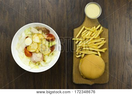 Caesar sauce salad cheeseburger fries delicious healthy food tomatoes croutons Parmesan cheese and fresh mozzarella junk food fast food cheese meat bad food not healthy
